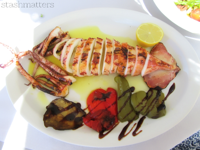 Eating freshly grilled squid / calamari - and Greek salad, of course.